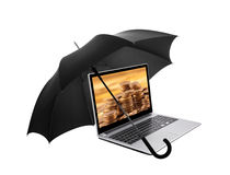 Laptop with coins protected by an umbrella Stock Image