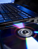 The laptop with a colorfull compact disc. The laptop with a compact disc Royalty Free Stock Photo