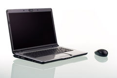 Laptop Computer. A modern laptop computer and wireless mouse with reflection on a glass surface Royalty Free Stock Image