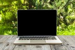 Laptop-Computer auf hölzernem Arbeitsplatz und Parkhintergrund Lizenzfreie Stockfotos