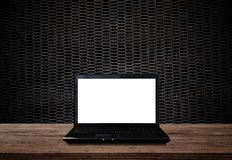 Laptop computer with blank screen, on wood table and black metal background. S Royalty Free Stock Image