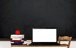 Laptop computer blank white screen, on wooden table in classroom Royalty Free Stock Images