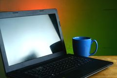 Laptop computer and a blue coffee mug Royalty Free Stock Photo