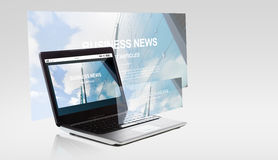 Laptop computer with business news on screen Stock Images