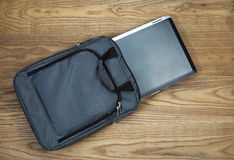 Laptop computer and carry case on faded wood Royalty Free Stock Image