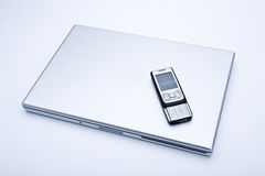 Laptop computer with cell phone. On it Royalty Free Stock Image