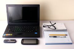 Laptop computer, cellphone, smartphone, notebook, pen, pencil and eyeglasses Stock Photo