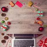 Laptop computer with Christmas decorations on wooden background. Christmas mock up template. View from above Royalty Free Stock Photo