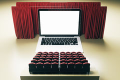 Laptop computer cinema front. Front view of abstract movie theater with laptop computer as screen, curtains and seats. Creativity and advertisement concept. Mock Royalty Free Stock Image