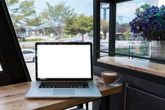 Laptop computer with coffee cup on wooden table. In cafe royalty free stock image