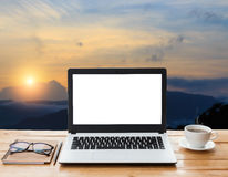 Laptop computer and coffee on wood workspace and mountain Stock Photos