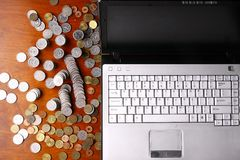 Laptop computer and coins Royalty Free Stock Images