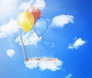 Laptop computer with colorful balloons flying high in blue sky Royalty Free Stock Photo