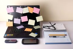 Laptop computer with colorful papers, cellphone, smartphone, notebook, pen, pencil and eyeglasses Stock Photography