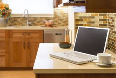 Laptop computer on counter in contemporary upscale home kitchen. Contemporary upscale home kitchen interior with cherry wood cabinets, quartz countertops and Royalty Free Stock Photo
