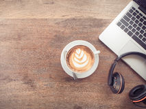 Laptop computer with cup of coffee and headphones on old wooden Royalty Free Stock Photo