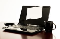 Laptop computer on desk with blank paper taped to the display screen. Image showing a laptop computer on a desk in between a black coffee mug and stapler with a stock photo