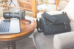 Laptop computer and dslr camera at cafe Royalty Free Stock Image