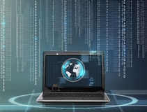 Laptop computer with earth globe on screen. Technology and network concept - laptop computer with earth globe on screen and binary code over gray background Stock Photo