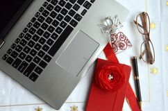 Laptop computer with a glass angel. And a yellow golden gift box. Technology and Christmas holidays at work theme royalty free stock photo