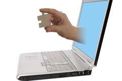 Laptop computer with hand holding piece of puzzle Royalty Free Stock Images