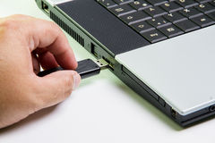 Laptop computer and hand with USB flash drive. selective focus Royalty Free Stock Photo