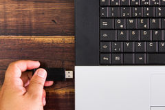 Laptop computer and hand with USB flash drive. selective focus Stock Photo