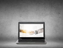Laptop computer with handshake on screen. Cooperation, partnership, technology and business concept - laptop computer with handshake on screen over gray concrete stock images
