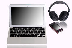 Laptop computer with headset and cellphone Royalty Free Stock Photo
