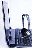 Laptop computer with headset on keyboard Stock Photo