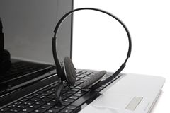 Laptop computer with headset on keyboard Stock Image