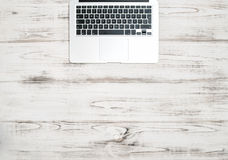 Laptop computer keyboard over wooden desk. Office background Royalty Free Stock Image
