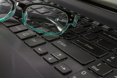 Laptop Computer Keyboard and Spectacles close-up. Shot at a shallow depth of field Royalty Free Stock Photo