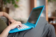 A laptop computer lies on the knees and hands working on its keyboard. Female hands working on a laptop keyboard. A laptop computer lies on the knees and hands Stock Photos