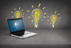 Laptop computer with light bulb on screen Royalty Free Stock Image
