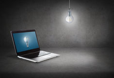 Laptop computer with light bulb on screen Stock Photo