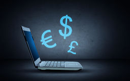 Laptop computer with lighting currency symbols Royalty Free Stock Photography