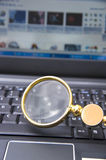 Laptop computer with magnifying glass Stock Photo