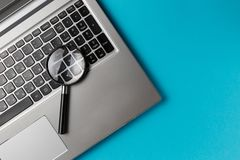 Laptop computer with magnifying glass royalty free stock photo