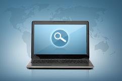 Laptop computer with magnifying glass on screen Royalty Free Stock Photo