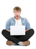 Laptop computer man shocked. Looking surprised at screen. Young modern male student model sitting cross legged on floor isolated on white background Royalty Free Stock Photos