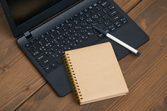 Laptop computer and memo note with ballpoint pen. On a wooden desk stock photo