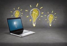 Laptop-Computer mit Glühlampe auf Schirm Lizenzfreies Stockbild