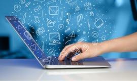 Laptop-Computer mit Hand gezeichneten Ikonen und Symbolen Lizenzfreie Stockfotos