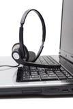 Laptop-Computer mit Kopfhörer auf Tastatur Lizenzfreies Stockfoto