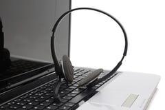 Laptop-Computer mit Kopfhörer auf Tastatur Stockbild