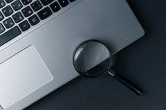 Laptop-Computer mit Lupe auf dunklem Hintergrund, Konzept der Suche stockfotografie
