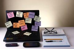Laptop-Computer mit Mitteilungen auf bunten Papieren, Mobiltelefon, Smartphone, Notizbuch, Stift, Bleistift und Brillen Stockbild