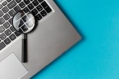 Laptop-Computer mit Vergr??erungsglas stockbilder