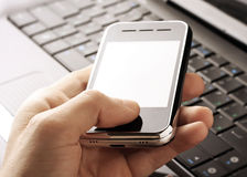 Laptop computer and mobile phone. In hand Stock Photo